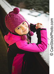 cute smiling girl posing on street at snowy winter day