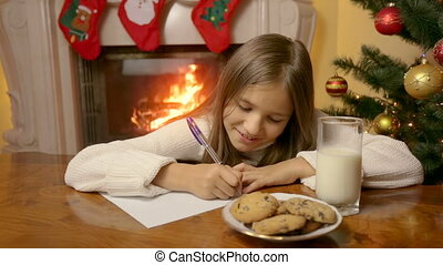 Portrait of cute smiling girl sitting behind table at living room and writing  letter to Santa Claus