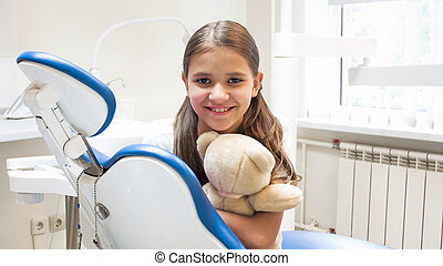 Portrait of cute smiling girl sitting in dentist chair and looking in camera