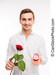 Portrait of cute smiling man, making proposal with wedding ring