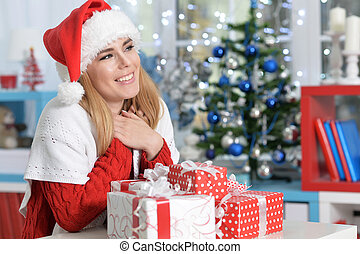 Portrait of cute smiling woman with Christmas gifts at home