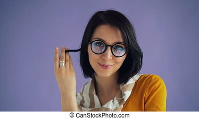 Portrait of cute student girl winding hair around finger...