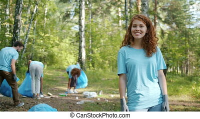 Portrait of cute female student turning to camera during volunteering work in forest while people are collecting garbage in background. Youth and ecology movements concept.