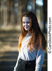 Portrait of cute teen girl with fiery red hair in the pine park.