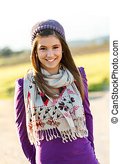 Close up portrait of cute teen girl with scarf and beanie outdoors.