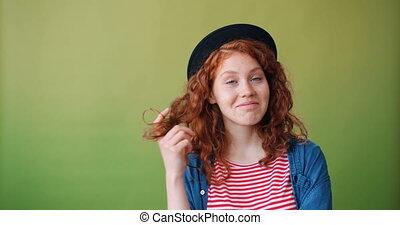 Portrait of cute teenage girl winding hair around finger...