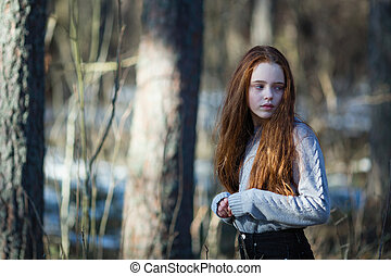 Portrait of cute teengirl with long bright red hair in the Park.