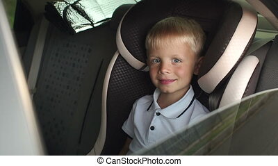 A cheerful baby waving his hand while sitting in a children's car seat.