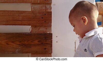 Portrait of cute toddler touching the wooden pallet outdoors...