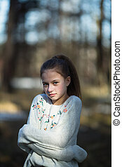 Portrait of cute twelve year old girl in the park.