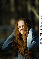 Portrait of cute twelve year old girl with fiery red hair posing in the pine park for a photoshoot.