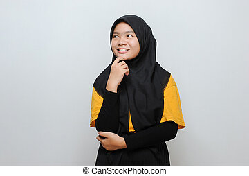 Portrait of Cute Young Asian Muslim woman smiling looking at copy space