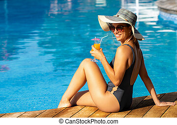 Portrait of cute young girl with sun hat and cocktail at swimming pool