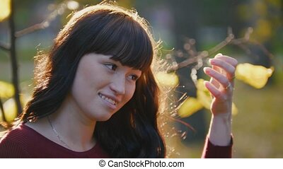 Portrait of cute young pregnant woman standing at autumn park among golden leaves, smiling and looking at sky, close up