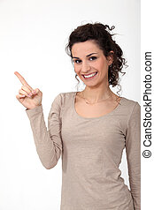 portrait of cute young woman all smiles pointing sideways