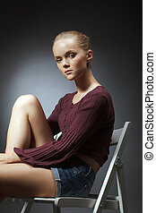Portrait of cute young woman sitting on chair