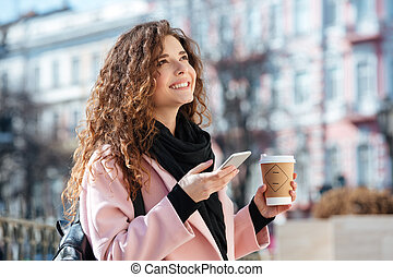 Portrait of cute young woman using smartphone outside.