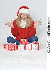 Portrait of cute young woman with present boxes