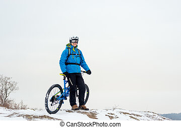 Portrait of Cyclist in Blue Resting with Mountain Bike on Rocky Winter Hill. Extreme Sport and Enduro Biking Concept.