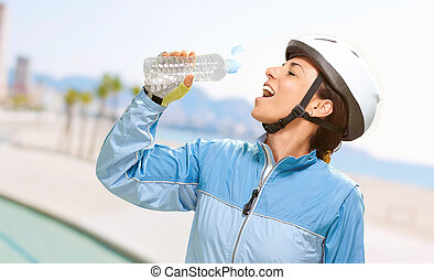 portrait of cyclist middle aged woman drinking water in the beach