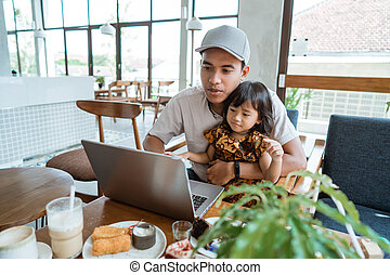 daddy with his daughter using laptop