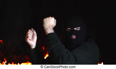 Portrait of dancing ultras man in balaclava against of...