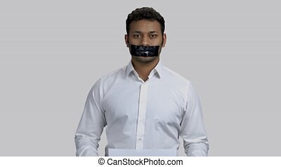 Portrait of dark-skinned hindu man with taped mouth. Showing 'silence' banner, grey isolated background.