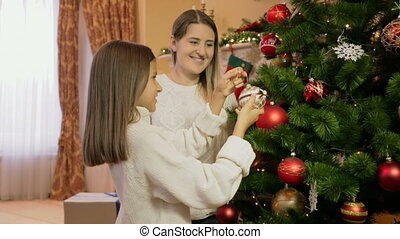 Portrait of daughter helps mother decorating Christmas tree with baubles and tinsel