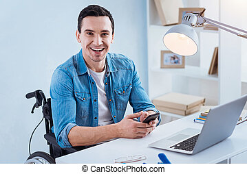 Portrait of delighted brunette that sitting at his workplace