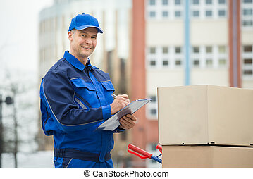 Portrait Of Delivery Man With Parcels And Clipboard -...