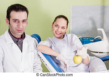 Portrait of dentist and his assistant with apple