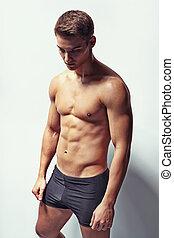 Portrait of depressive young muscular man in underwear...