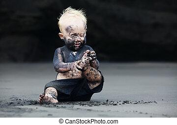 Portrait of dirty child on the black san beach
