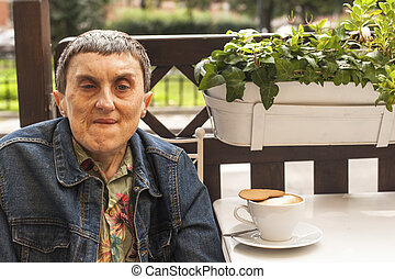 Portrait of disabled man with cerebral palsy sitting at outdoor cafe with a cup of coffee.