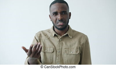 Portrait of displeased African American man knocking at head expressing disagreement saying Are you crazy on white background. People and expressions concept.