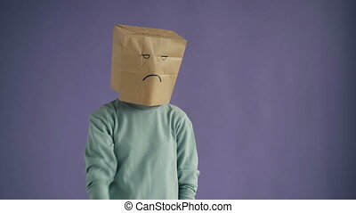 Portrait of displeased person with paper bag on head showing...