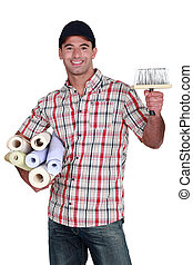 portrait of do-it-yourselfer carrying wallpaper rolls and...