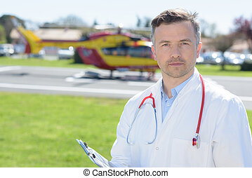 Portrait of doctor, air ambulance in background