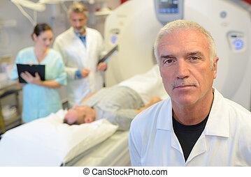 Portrait of doctor, man on scanner in background