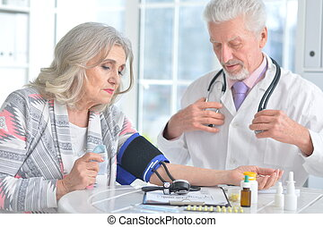 Portrait of doctor measuring blood pressure of woman