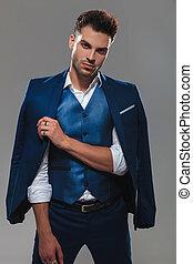 portrait of dominant gentleman holding blue suit collar...