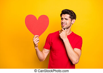 Portrait of doubtful guy celebrate 14-february date get red big paper card heart think disagree dislike wear modern clothing isolated over yellow color background