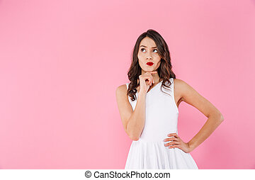 Portrait of dreaming asian woman 20s with dark long hair in white dress looking upward on copyspace with brooding gaze, isolated over pink background