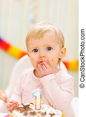 Portrait of eat smeared baby eating first birthday cake