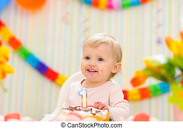 Portrait of eat smeared kid with first birthday cake