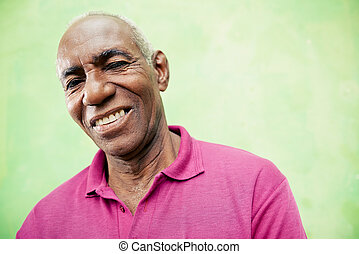 Portrait of elderly black man looking and smiling at camera...