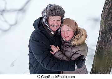 Portrait of elderly couple having fun outdoors in winter forest