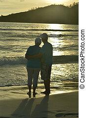 Portrait of elderly couple on beach. Travel.