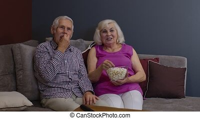 Portrait of elderly couple watching TV at home eating popcorn enjoying film together at home