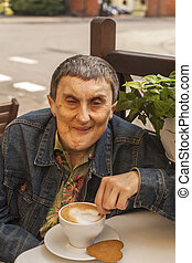 Portrait of elderly disabled man with cerebral palsy, at an outdoor cafe.